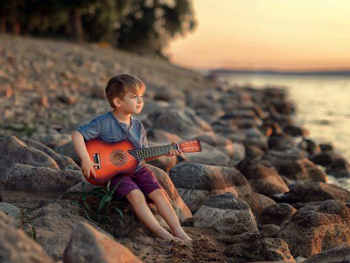 small boy guitar on rock stones